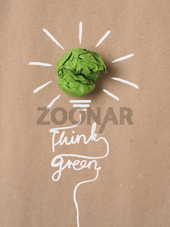 Recycled paper background with green crumpled paper ball as light bulb, ecology concept, innovations, renewable energies