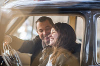 Happy couple in vintage car with presents on roof