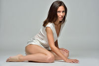 beautiful barefoot woman in white blouse is sitting on the floor