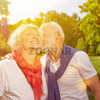 Alter Mann küsst Seniorin auf Wange im Sommer
