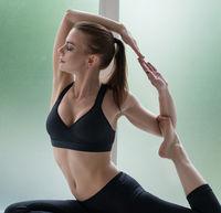 Pretty model on the window sill in yoga pose