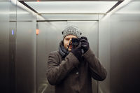 Male photographer taking a self picture in an elevator. Mirror selfie portrait, learning photography and analog film look concept.