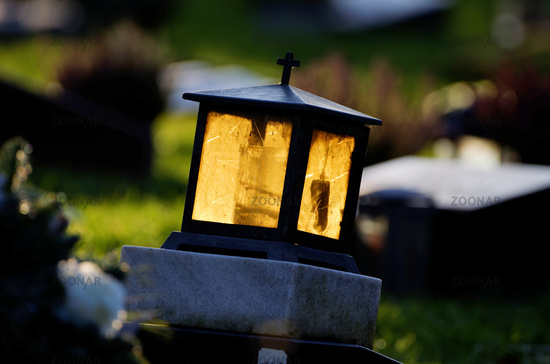grave lantern with yellow glass shining in the back light on a gravestone in a cemetery