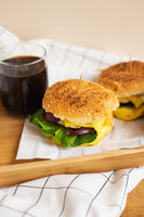 Large and tasty grilled hamburgers with sesame seeds lie on a wooden tray with a glass of cola. Wooden table and white checkered napkin. Close-up.