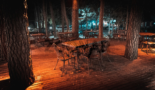 Night scene of wooden deck of an elegant outdoor bar, illuminated by small lamps in the trees that rise over the terrace
