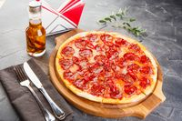 Pepperoni pizza on wooden board on dark background. Close-up
