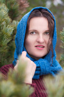 Portrait of brunette standing in pine forest. Woman dressed in brown pullover, blue scarf over head