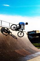 BMX stunt vertical. A professional cyclist Extreme cycling concept. Dert jump. BMX vertical barspin jump. BMX Freestyle Vert Stunt. Halframp