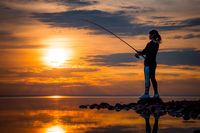 Woman fishing on Fishing rod spinning in Norway.