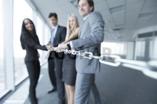Businessmen pulling chain