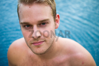 Young handsome shirtless man with blond hair in the swimming pool