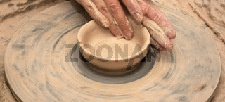 Woman hands in clay at process of making clay bowl on pottery wheel