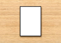 Black picture frame hanging on a light wooden wall