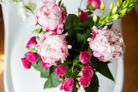 A beautiful bouquet of tender pink peonies and small roses stands on a white chair. Wedding bouquet, birthday. Close-up.