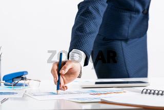 Businesswoman standing near office desk with pen