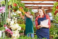Frau in Gärtnerei arbeitet Checkliste ab