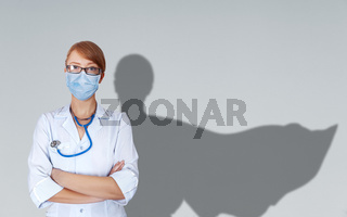 Concept of brave medical doctors in uniform and mask with shade of fluttering cape behind her shoulder.