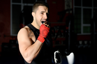 Boxing fighter putting on mouthguard.