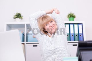Businesswoman working and stretching her arms behind head indoors at home office. Work, relaxation and homeoffice concept.