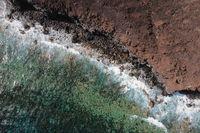 Aerial top view of waves splashing on rocky volcanic coastline. High quality photo.