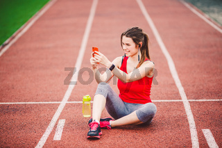 beautiful fitness girl uses smartphone at stadium after workout. Sports and healthy. Sport woman use of cellphone inside sport complex. Sport and technology. resting after workout, run at red track