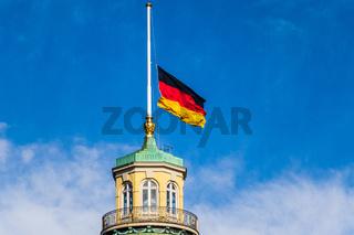 Close view on German Flag at Halfmast, auf Halbmast, on the top of Castle Karlsruhe. District Karlsruhe, Baden-Württemberg, Germany