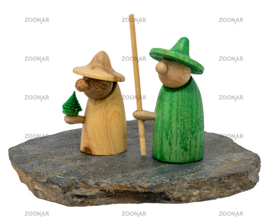 Two wooden christmas figure stand on a dark wooden board isolated on white