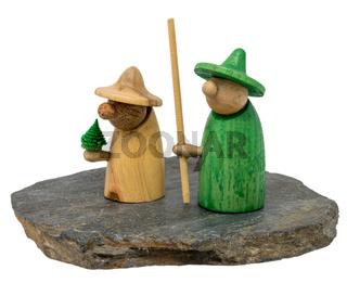 Zwei Wichtel Figuren aus Holz stehen auf einem dunklen Holzbrett freigestellt auf weiß