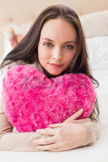Pretty brunette holding heart cushion on bed