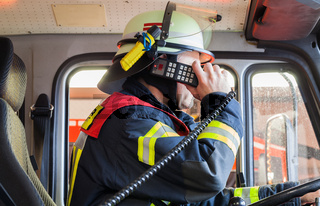 Feuerwehrmann am Funkgeraet im Einsatzwagen