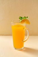 jug with orange juice and peppermint on table