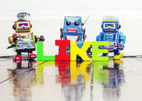the word LIKE with retro robot toys on old wooden floor