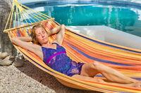 Dutch woman relaxing in hammock near pool