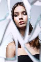 Young woman looks in a broken mirror. Portrait of beautiful female in the mirror shards