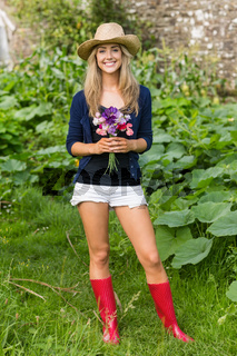 Pretty blonde smiling at camera holding flowers