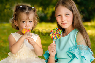 sisters with sweet lollipops in nature in the summer in the park