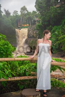 Beautiful woman posing against the background of muddy waters of Tegenungan waterfall