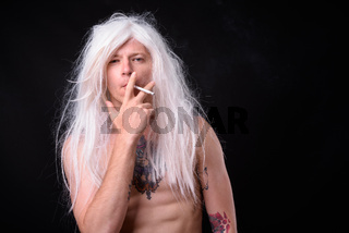 Punk rocker man wearing wig against black background