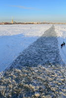 People walk along the frozen canal, punched by an icebreaker on