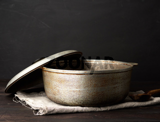 aluminum old cauldron on a wooden table, kitchen utensils