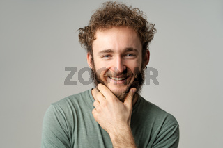 Handsome young guy posing in studio in olive t-shirt looking at camera touching his chin isolated on white background. Portrait of smiling young man with hands folded