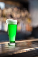 Glass of light green beer on a background of pub.