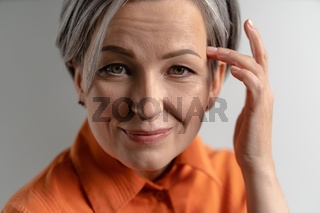 Portrait of mature Caucasian woman with gray hair touching to her temple with fingers. Close up shot of female face on white background. High quality photo