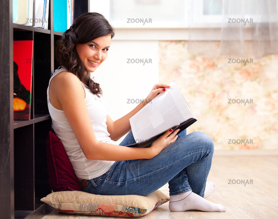 student with a lbook in a library