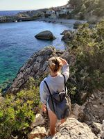 Young active feamle tourist wearing small backpack walking on coastal path among pine trees enjoing beautiful costal view of Velo Zarace beach on Hvar island, Croatia. Travel and adventure concept
