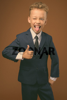 Young boy as businessman against brown background