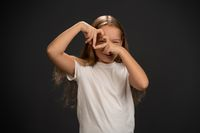 Love gesture happy 8,10 years old girl holding her hands together making a heart shape and looking thru it wearing white t shirt smiling at the camera isolated on dark grey or black background