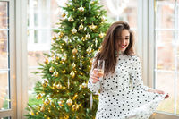 Happy woman with champagne against Christmas tree