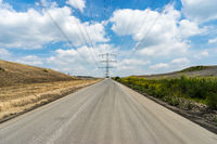 Road through a landfill with high-voltage mast