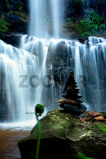 Zen waterfall with lush foliage and balancing stones